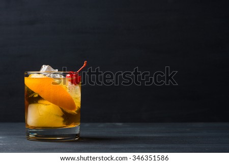 Old fashioned cocktail with cherry and orange peel #346351586