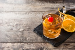 Old fashioned cocktail with orange and cherry on wooden table. Copyspace