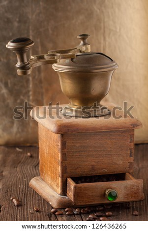 Old Fashioned Coffee Grinder And Roasted Coffee Beans On Brown Wooden Table Stock Photo