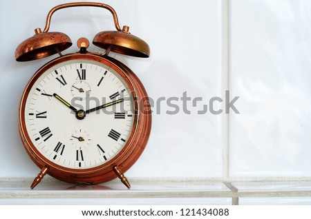 old-fashioned copper alarm clock on the mantelshelf
