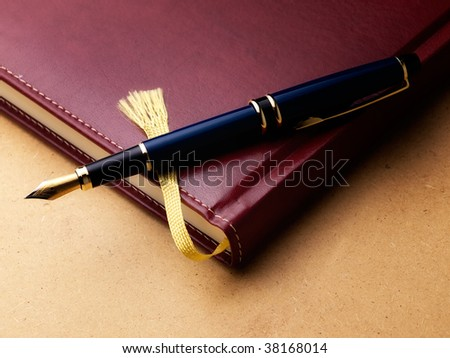 Old fashioned diary or log book with a fountain pen  on a grungy background.