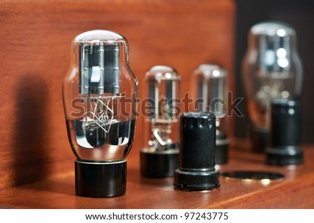 Old-fashioned electronic device amplifier bulb diode lamp for sound reproduction close-up - stock photo