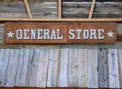 Old fashioned general store sign mounted on the wooden exterior of a rustic building. Copy space