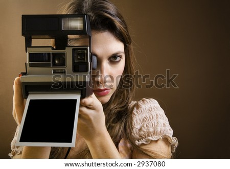 old-fashioned: girl taking a picture with an old instant photo