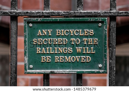 Old fashioned green cast iron public warning sign about bicycles being removed if they're secured to the railings.