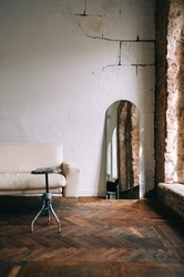 Old fashioned interior big wooden window and mirror, white sofa in old vintage living room with brick walls.