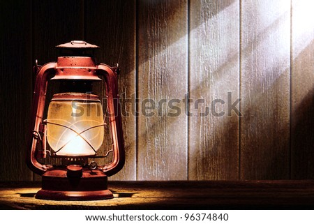 Old fashioned kerosene lantern style oil lamp burning with a soft glow light in an antique rustic country barn lit by diffused sunlight shining on a wood plank wall through a window
