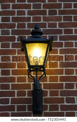 Old-fashioned lamp on brick wall during night #752305441