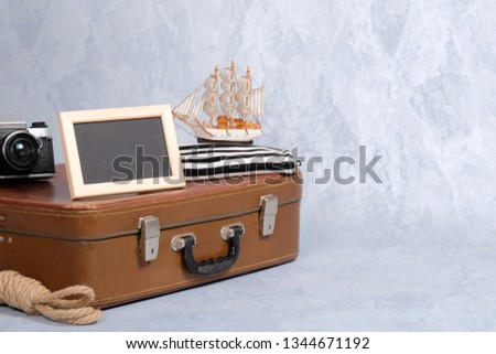 old fashioned leather suitcase, picture frame with blank black space for text, sailboat toy, retro photo camera, rope. Clothing and personal accessories of sailor, nautical and marine style concept
