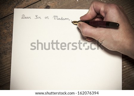 Old fashioned letter with a pen in a hand