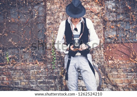 Old fashioned man photographing with vintage medium format photo camera.