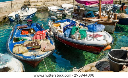 Old-fashioned mediterranean fishing boats with colorful bags and nets moored. Petrovac marina, Montenegro
