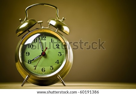 Old fashioned metal alarm clock on a brown background.