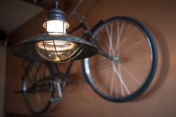 Old fashioned metal light fixture with an incandescent light bulb with an old fashioned retro bicycle hanging on the wall behind it