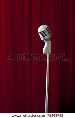 Old fashioned microphone on red curtain background