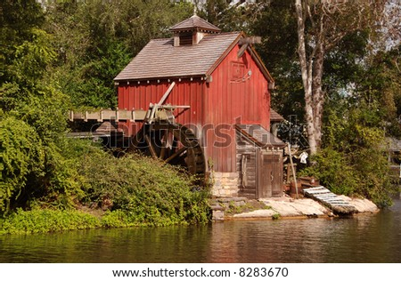 Old fashioned mill on a river - stock photo