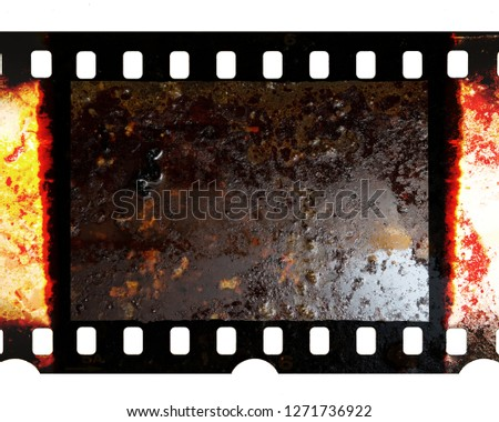 Old fashioned 35mm filmstrip or dia slide frame with burned edges isolated on white background. Real analog film scan with signs of usage. Dirty film material.