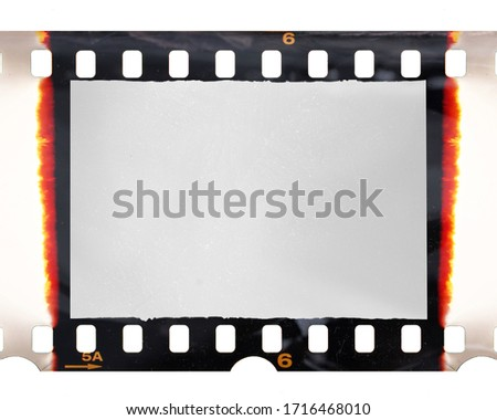old fashioned 35mm filmstrip or dia slide frame with burned edges isolated on white background. Real analog film scan with signs of usage and foil effect.