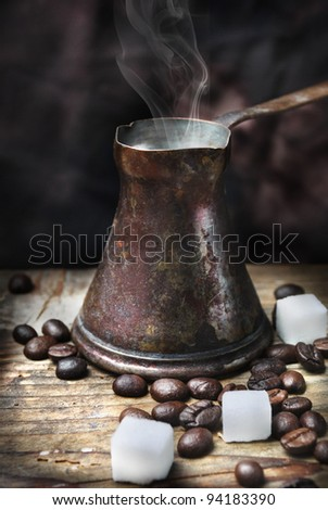 Old-fashioned oriental coffee pot on grunge wooden plank
