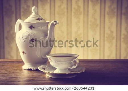 Old-fashioned porcelain jug with a cup of tea with old-fashioned wallpaper background