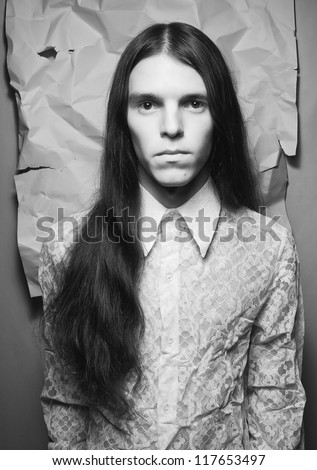old fashioned portrait of a long-haired boy over background of wrinkled white paper. black and white studio shot