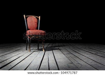Old fashioned red chair on a wooden floor