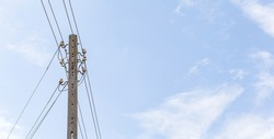 Old fashioned retro medium voltage power lines single pole with cables, wires. Blue sky simple high resolution wide background, banner, copy space. Power generation and transmission industry concept