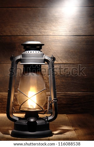 Old fashioned rustic kerosene oil lantern lamp burning with a soft glow light in an antique country barn