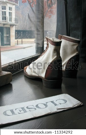 Old-fashioned shoes sit in window of Historic Downtown Harper's Ferry, West Virginia - closed sign
