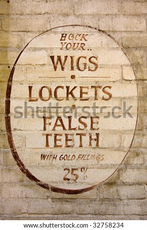 "Old fashioned sign inviting you to ""hock"" your wigs, lockets and false teeth."