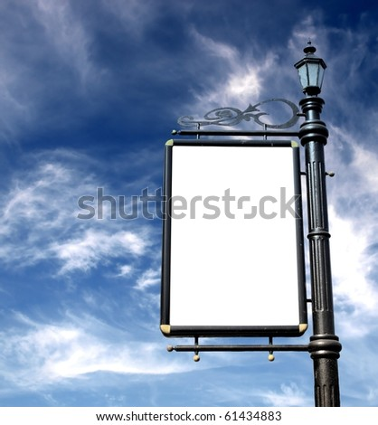 Old-fashioned street lantern with blank  board on bright blue sky
