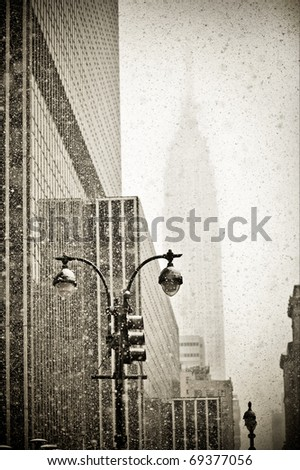 Old-fashioned stylization of silhouette of Empire State building in blizzard