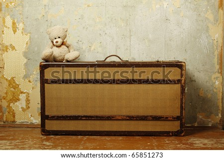 Old-fashioned suitcase standing on the old wooden floor against a shabby walls, suitcases sitting on the edge of  Teddy. Forgotten, abandoned