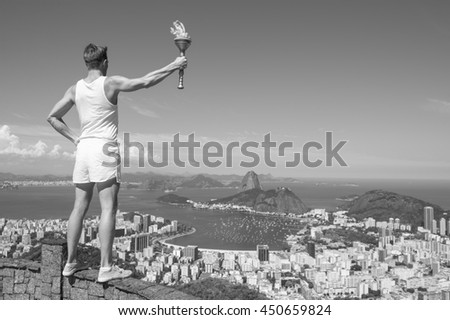 Old-fashioned torchbearer athlete in classic vintage white sports uniform standing holding sport torch at black and white city skyline overlook in Rio de Janeiro, Brazil