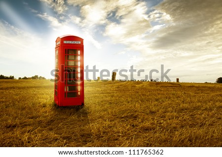 Old-fashioned traditional red telephone booth or public payphone standing in an open deserted field in evening light