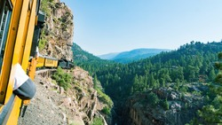 Old-fashioned train of the touristic route from Durango to Silverton (USA), running close to a cliff. Green valley on the right.