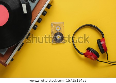 Old-fashioned vinyl player, headphones, audio cassette on yellow background. Media 70s. Top view