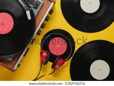 Old-fashioned vinyl player with records, Retro headphones on yellow background. Media 70s. Top view