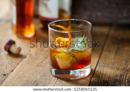 Old fashioned, whiskey drink with rosemary ice cubes