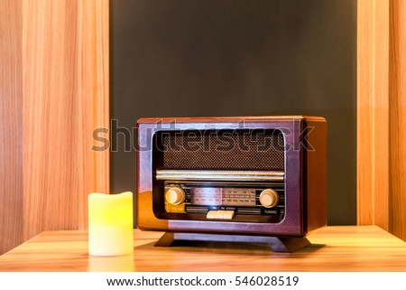 Old-fashioned wooden radio set and a yellow candle on a table. #546028519