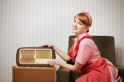 Old-fashioned young woman listening to the radio