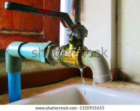 Old faucets leak, faucet leaks on the wash basin, wasting money and resources in vain. On the background, walls and windows: conservation of water concepts. #1320931655