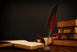 Old feather quill ink pen with inkwell and old books over wooden desk in front of black wall background. Conceptual photo on history, fantasy, education and literature topic.