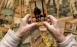 Old female hands hold old travel photo. Vintage photo cards on the wood background. Remembering Paris. European tourism and vacation travel. Memory and dreams concept.