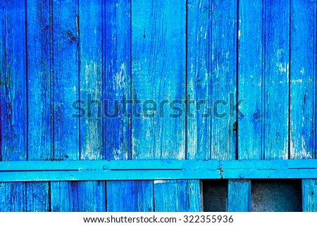 Old fence planks painted in bright blue color