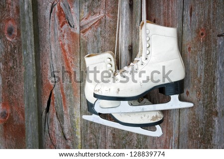 Old figure ice skates hanging on a red rustic wooden wall