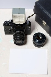 Old film camera, removable lens and wired flash. They lie on the surface of the table. Near a white sheet of photo paper.