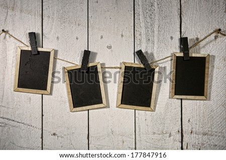Old Film Looking Chalkboards Hanging on a Rope Held By Clothespins