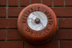 Old fire bell on a brick wall