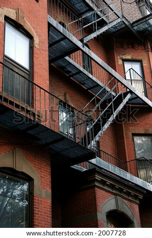 old fire escape zig zags down the side of an old brick apartment building in boston\'s beacon hill district